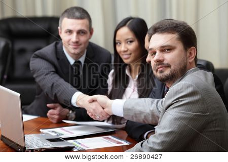 Multi ethnic business team at a meeting. Interacting. Focus on caucasian man in front