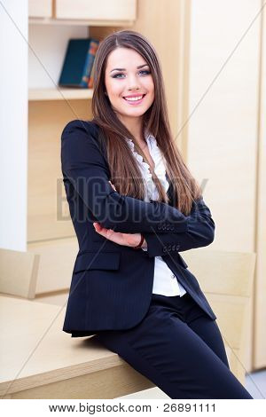 Joven empresaria feliz en traje de pie cerca de la mesa en la oficina