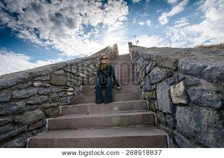 Adult Female Sitting On The Forty Steps On The Rhode Island Cliff Walk On A Spring Day