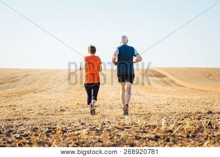 Senior woman and man running or jogging on a field to remain fit and healthy