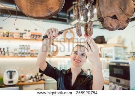 Sales clerk in deli cutting sausages to sell them to customers