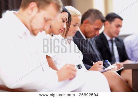 Empresarios sentado en una fila en la reunión y hacer anotaciones. Centrarse en la mujer