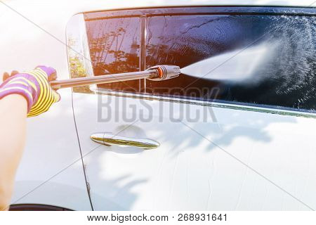Manual Car Wash With Pressurized Water Outside. Summer Car Washing. Cleaning Car Using High Pressure