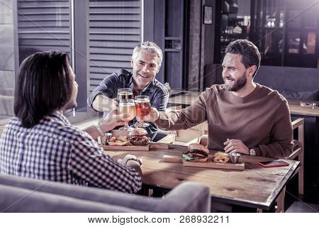 Cheerful Young Males Touching Bocals With Beer