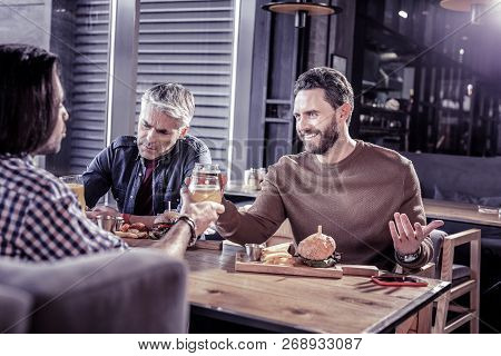 Positive Delighted Young Man Touching Bocals With Partners