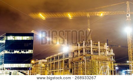 Lots Of Tower Cranes Build Large Residential Buildings At Night. Buildings Under Construction, Crane