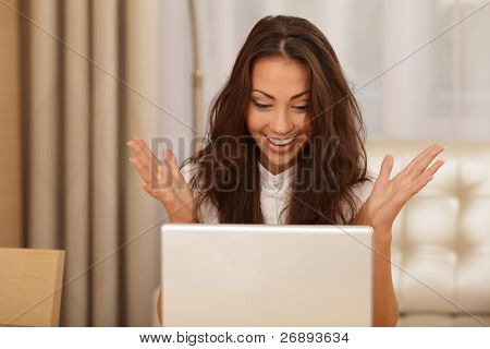Portrait of surprised and happy young woman with a laptop
