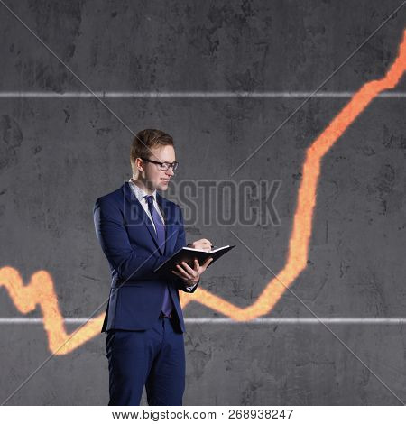 Businessman with organizer standing on a diagram background. Business, office, success, concept.