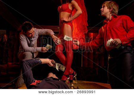 View of three men offering money to a stripper on stage