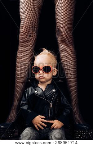 We Will Rock You. Small Child Boy In Sunglasses And Rocker Jacket. Small Boy At Female Legs. Rock St