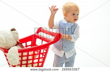 Shopping For Children. New Arrivals. Happy Childhood And Care. Little Boy Go Shopping With Full Cart