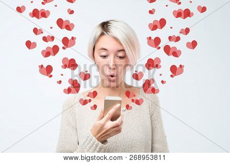 Girl Looking At Mobile Phone Screen In Surprise Reading Sms. Declaration Of Love Concept