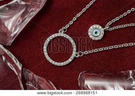 Silver Necklace Including Lucky Charm On Felt Surface With Pieces Of Glass