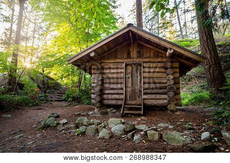 Log Cabin In A Forest In The Summer In Lighthouse Park.