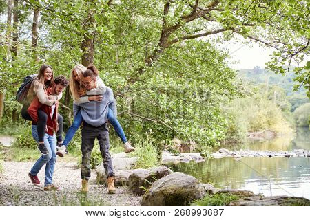 Four adult friends during a hike, men piggybacking their girlfriends