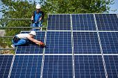 Two technicians working with electrical screwdriver connecting shiny solar photo voltaic panel to metal platform system on green tree thick foliage background. Green energy production concept. poster