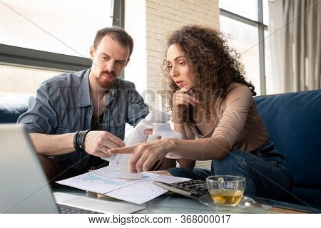 Young confident businesswoman pointing at laptop screen while making presentation of new ideas for project to business partner