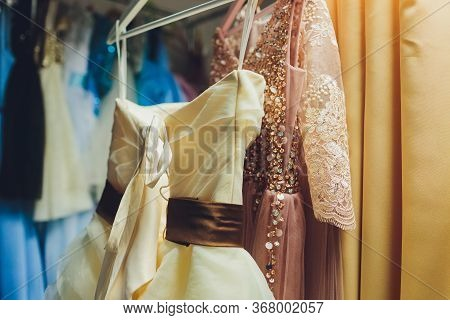 Many Ladies Evening Gown Long Dresses On Hanger In The Dress Rent Shop For The Wedding Day. Dresses