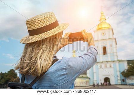 Woman traveler tourist using smartphone, taking photo of church Kiev, Ukraine in summer sunny day. Enjoying European, Famous popular touristic place in world.
