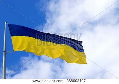 Large National Flag Of Ukraine Flies In The Sky. Big Yellow Blue Ukrainian State Flag In The Dnepr C