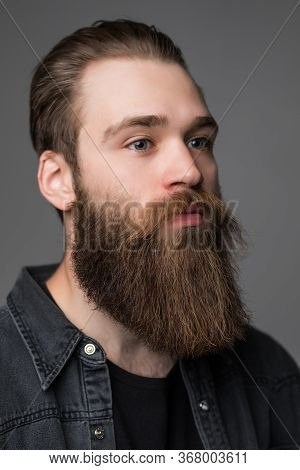 Young Handsome Bearded Man While Standing Against Grey Background