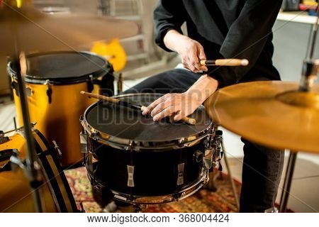Hand of young musician putting drumstick on black drum while sitting in front of drumset and hitting cymbal during rehearsal in garage