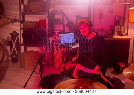 Young serious musician in casualwear looking at you while sitting by drumset in garage on background of laptop, musical instruments and worktools