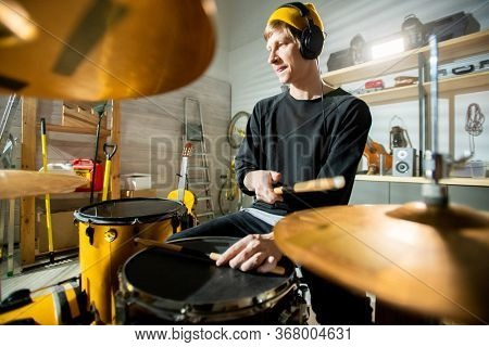 Young man with drumsticks sitting in front of drumset and recording music in garage or his own studio on background of worktools