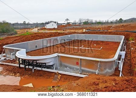 A New In Ground Swimming Pool Being Installed In A New Housing Development