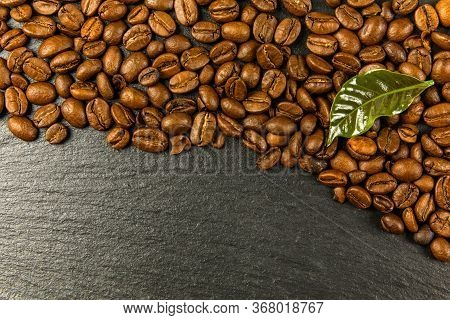 Coffee Beans On A Black Background. Energy Stimulant And Smooth Java Concept. Coffee Beans With Leav