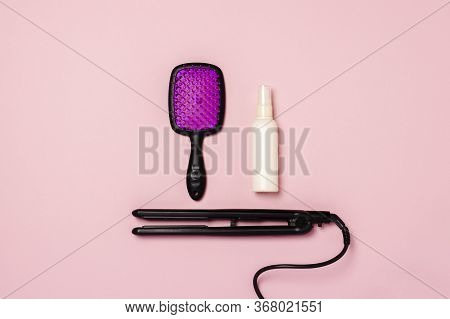 Hair Straightener, Comb And Hair Care Product On A Pink Background. Concept Of Hair Care, Hairstyle,