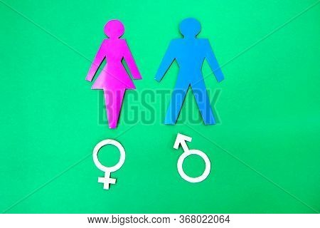 Figures Of A Man And A Woman With Gender Sign On Green Background.