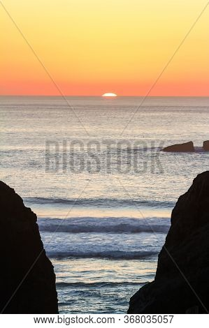 Bright Orange Sun Setting Behind The Horizon Casting Warm Tones Across The Sky Silhouetting The Rock