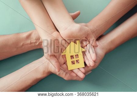 Adult And Child Hands Holding Paper House, Family Home, Homeless Housing And Home Protecting Insuran