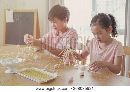 Mixed Race Young Asian Children Building Tower With Spaghetti And Marshmallow Learning Remotely At H