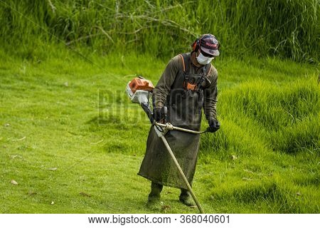 La Calera, Colombia - May, 2020: Man Scything Wearing Safety Personal Protective Equipment And Face
