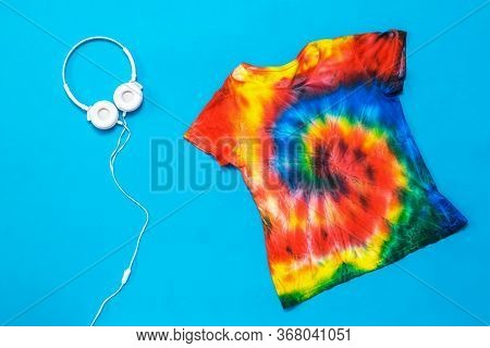 T-shirt In The Style Of Tie Dye And White Headphones On A Blue Background. White Clothes Painted By