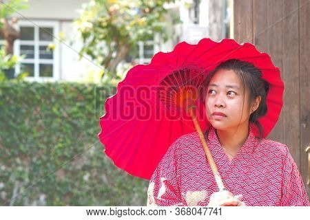 Soft Focus On Traditional Japanese Yukata Young Girl With Red Umbrella In Garden, Asian Girl In Yuka