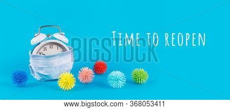 Alarm Clock In Medical Mask And Plastic Balls As Viruses On The Blue With Time To Reopen Wording. Co