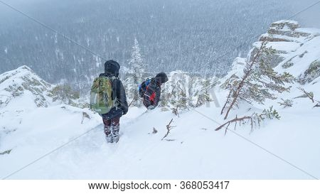 A Group Of Tourists With Backpacks On Their Shoulders Descends From The Top Of A Snow-covered Mounta