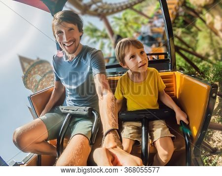 Father And Son Having Fun On Rollercoaster