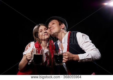Happy Oktoberfest Couple In National Ethnic Dress Clinking Beer Mugs And Black Background. Girl And