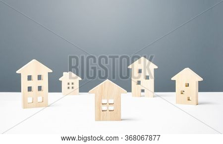 Many Wooden Figures Of Residential Buildings. Affordable Comfortable Housing. Urban Studies And Scie