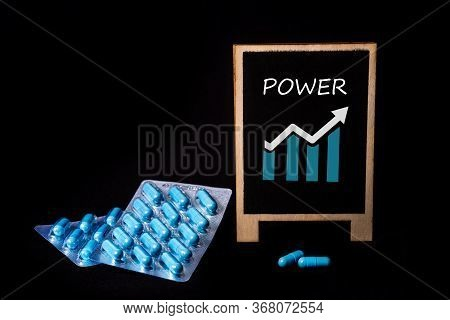 Two Packs Of Blue Capsules And The Word Power On A Chalkboard. Pills For Mens Health And Sexual Ener