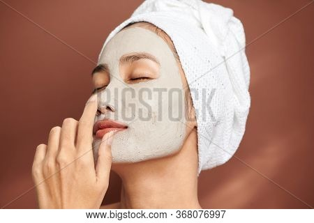 Close Up Shot Of Beautiful Asian Woman Applies Purifying Mask On Face, Has Beauty Treatments