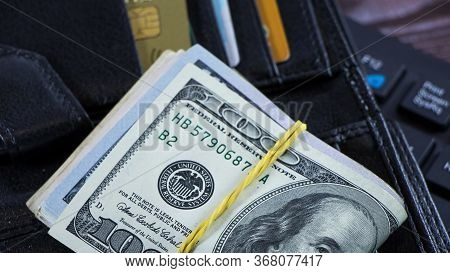 A Stack Of Hundred-dollar Bills Is On The Wallet In The Form Of A Bribe Or Corruption. Dirty Money O