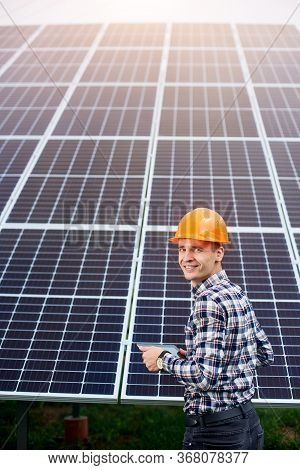 Sun Battery Station And Worker In A Helmet And With A Tablet In His Hands Near It. Green Ecological