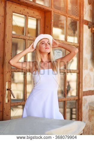 Charming Young Woman In The Summer Sun Light In A White Dress And With A Hat On The Street Of The To