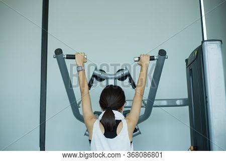 Young Fitness Girl Execute Exercise With Exercise-machine In Gym