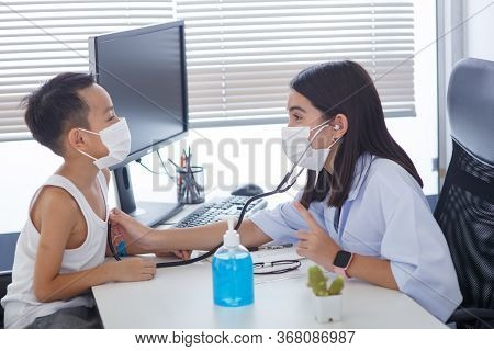 An Asian Female Doctor Wearing A Surgical Mask Is Pouring Alcohol Gel On The Patient's Hand.